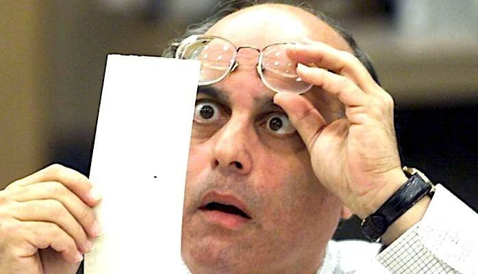 Examining a ballot for punch hole in 2000