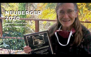 Picture of Carol Greenough holding the 2020 Maurine Neuberger award with trees in the background