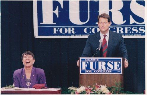 Elizabeth Furse sitting and Al Gore standing at a podium.